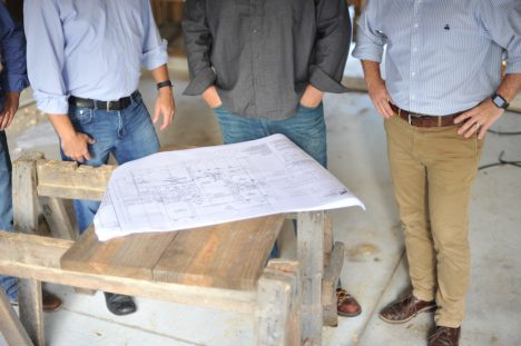 Three men standing around a wooden saw horse with blueprint plans open
